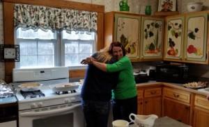 Jims mom, Julie, hugging Sheri, his sister in the kitchen