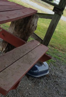 Broken picnic table at pavilion held up by a stump and the top of a grill