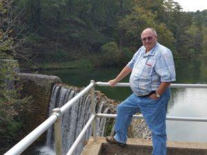 Jim at the dam that forms lake behind him