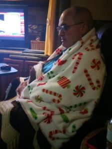 Jimmy, wearing his snuggy on top of clothes and two blankets