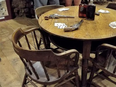 Table and seat where Hickok sat, his guns, & the hand he held upon his death